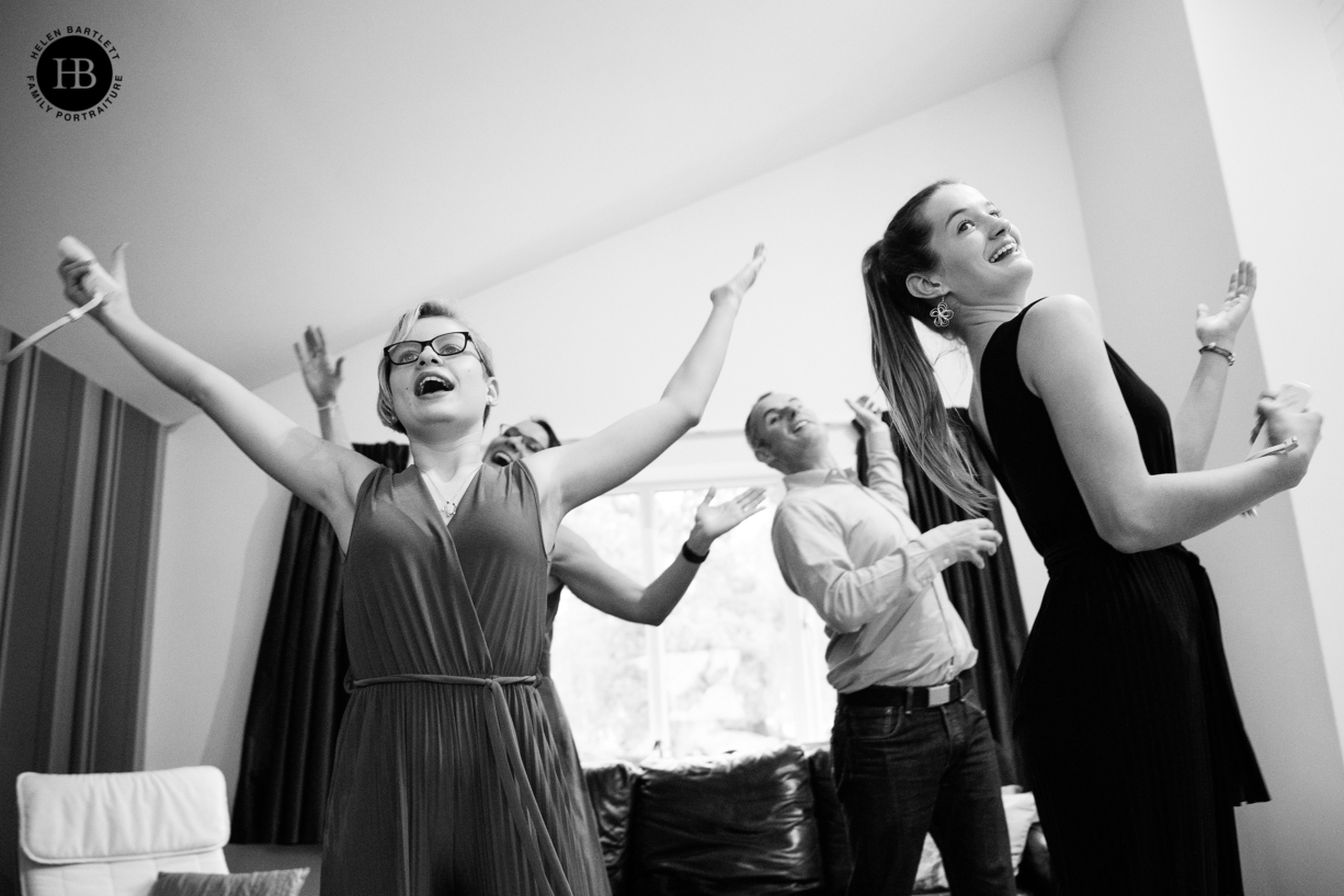 teenage girls play wii dance while wearing formal dresses on family photo shoot