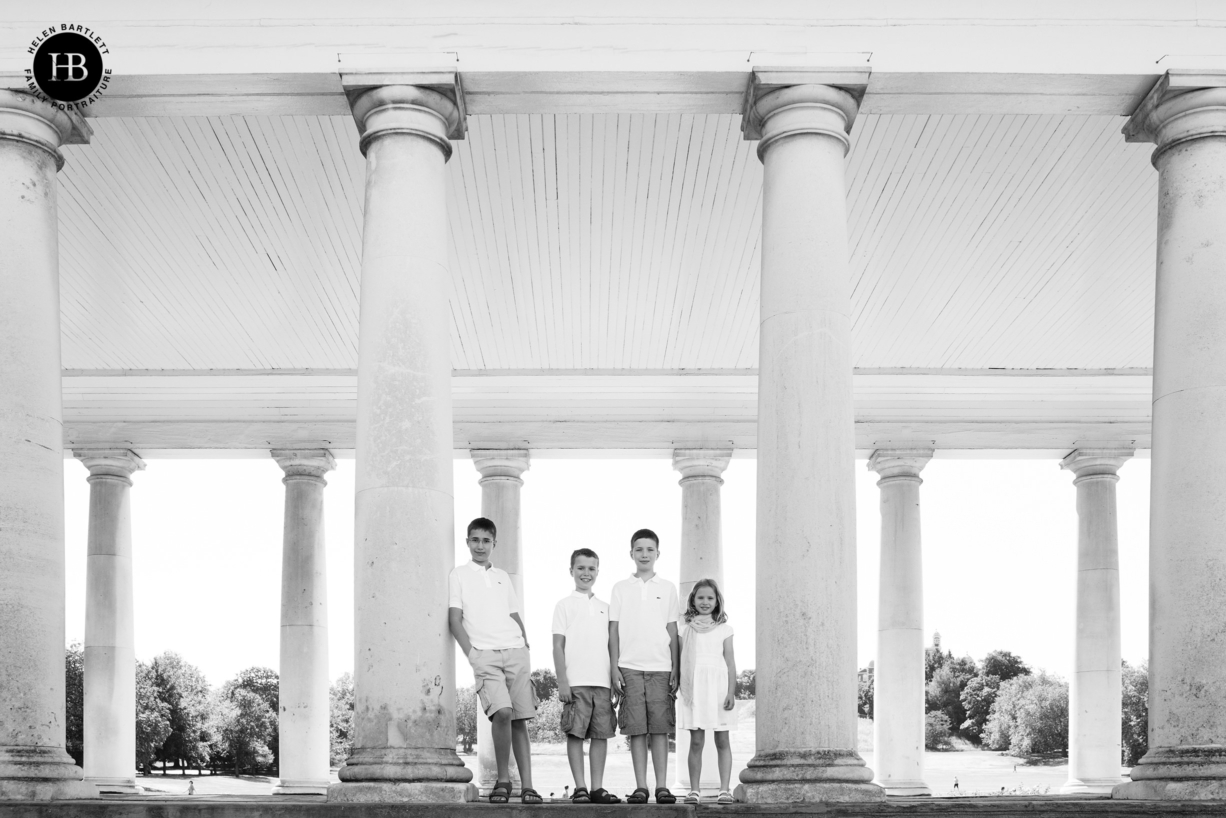 four children in matching white outfits formally pose on a family photo shoot in London