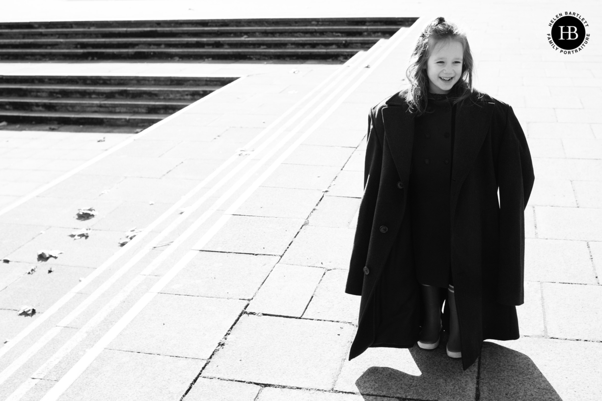 little girl wears dads coat in humorous picture to show importance of trying on clothes for a family photo shoot