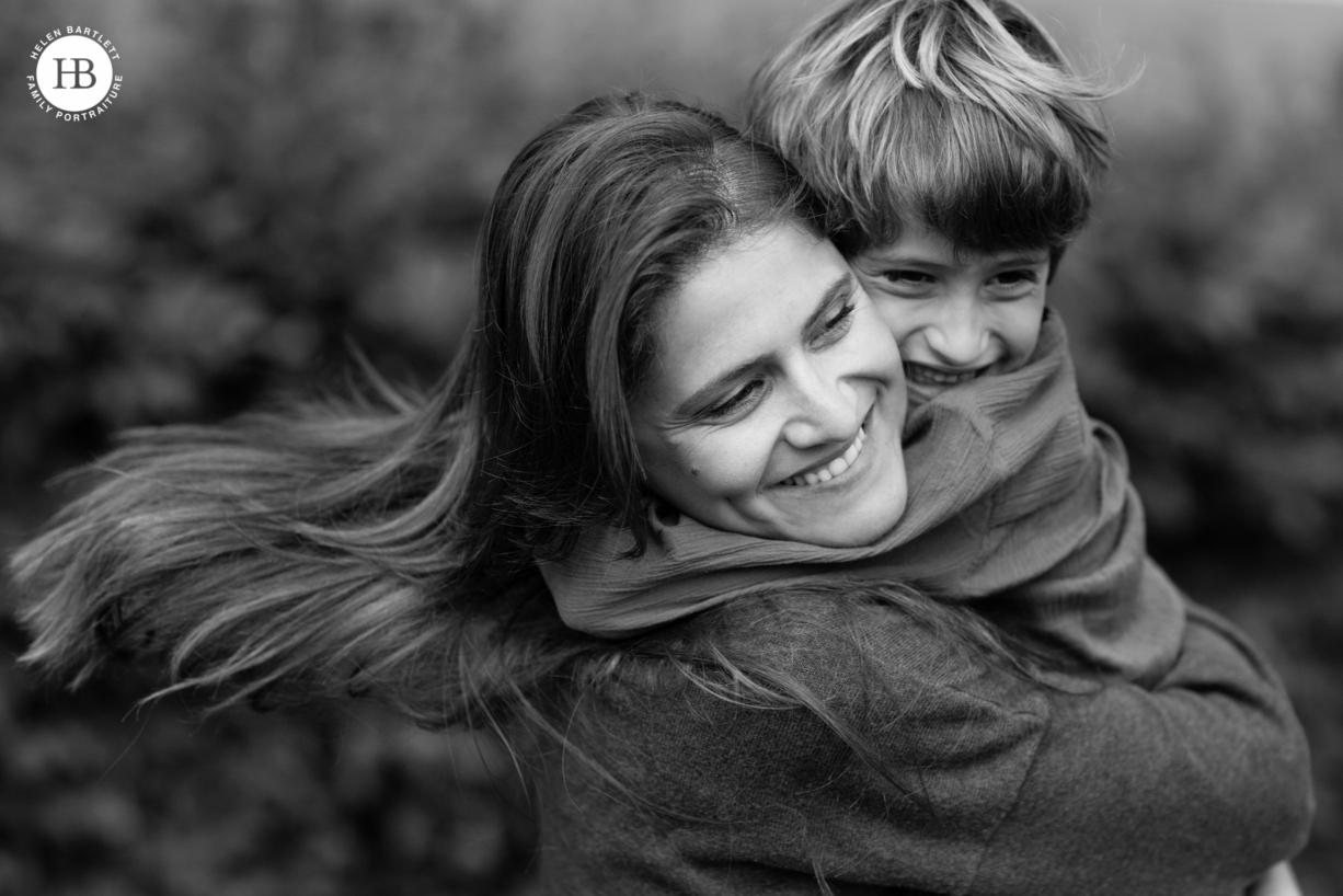 mum and son hug wearing plain coloured tops