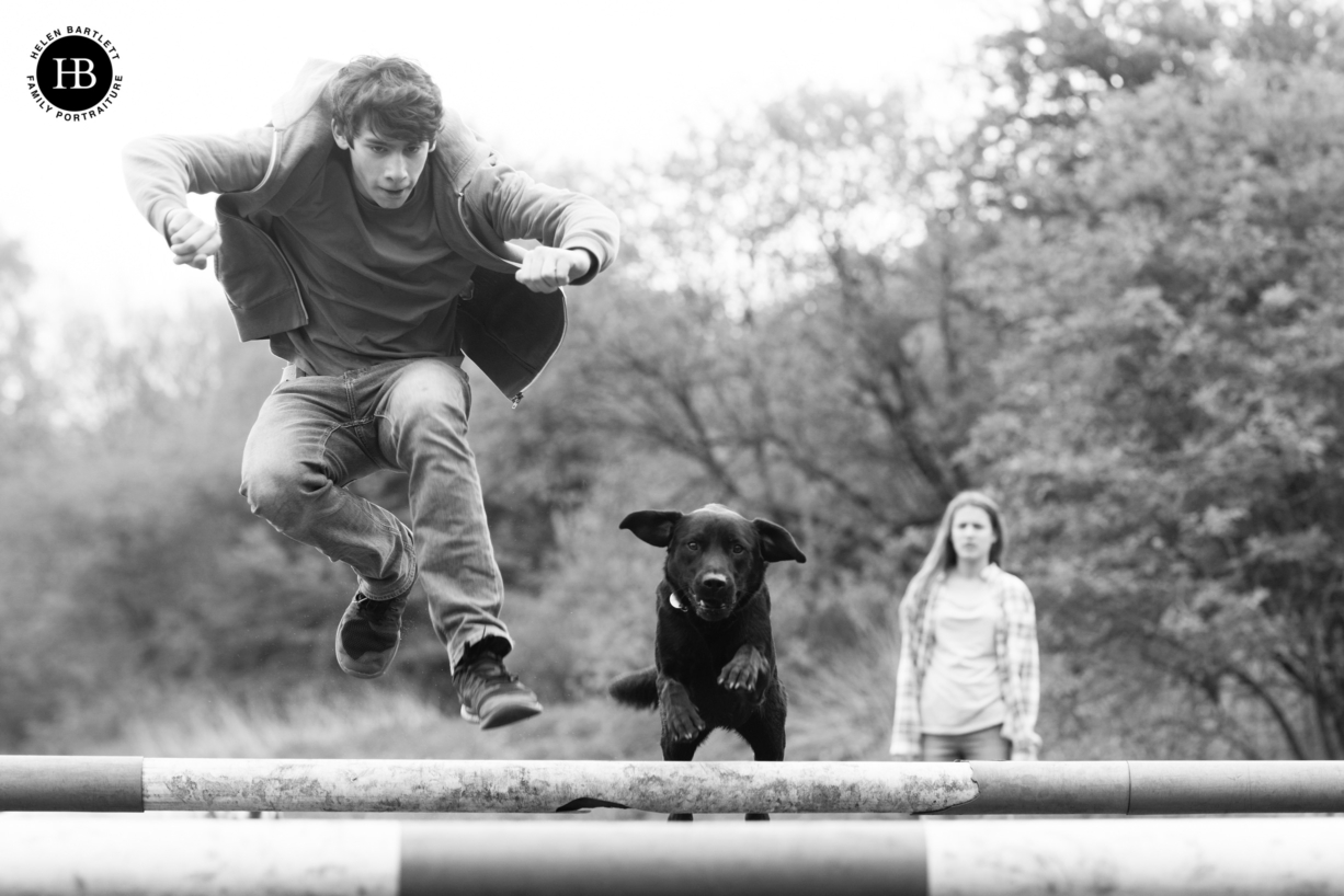 teenage boy plays with dog jumping over show jumps