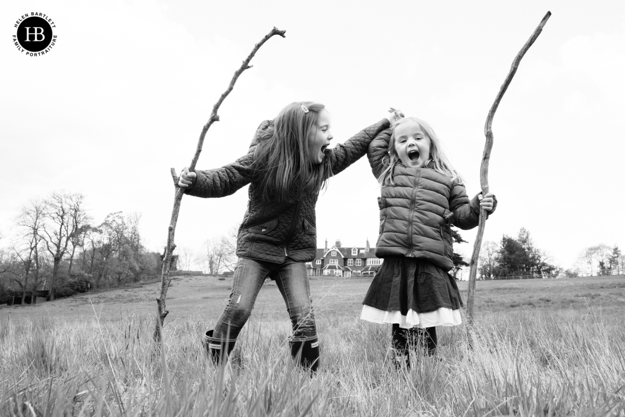 two little girls laugh holding sticks, one wearing a skirt the other wearing trousers. Dress for your personality when choosing your outfit for family photo shoot