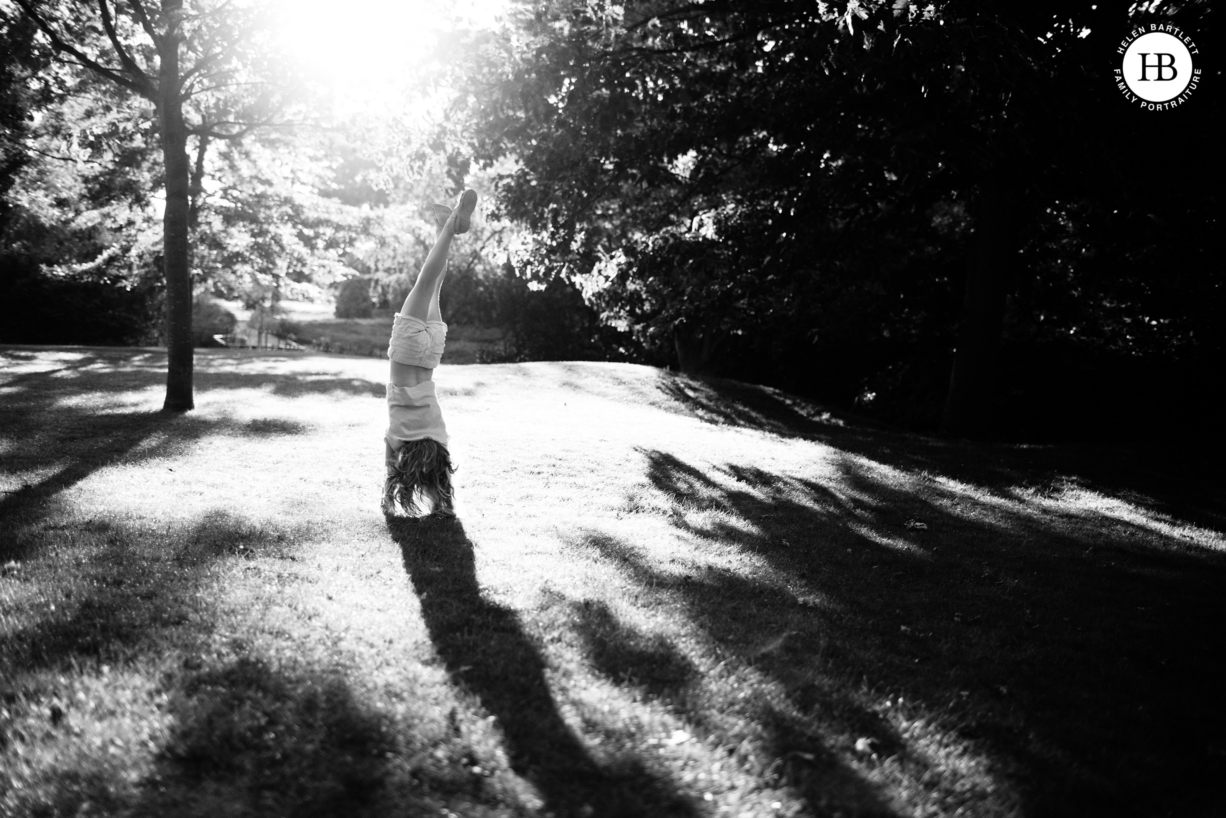little girl does a handstand in the park in evening light