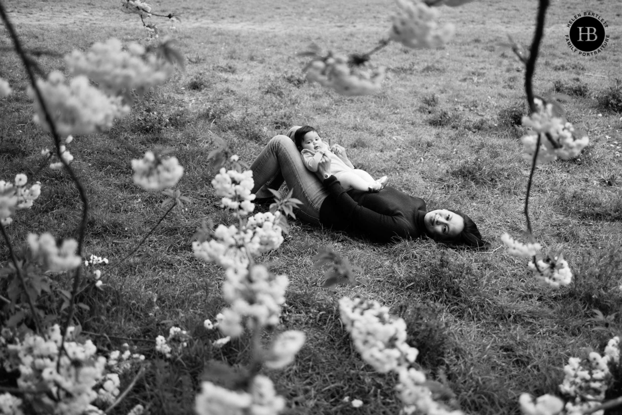 mother-and-baby-lie-on-grass-framed-by-blossom-battersea-park-london