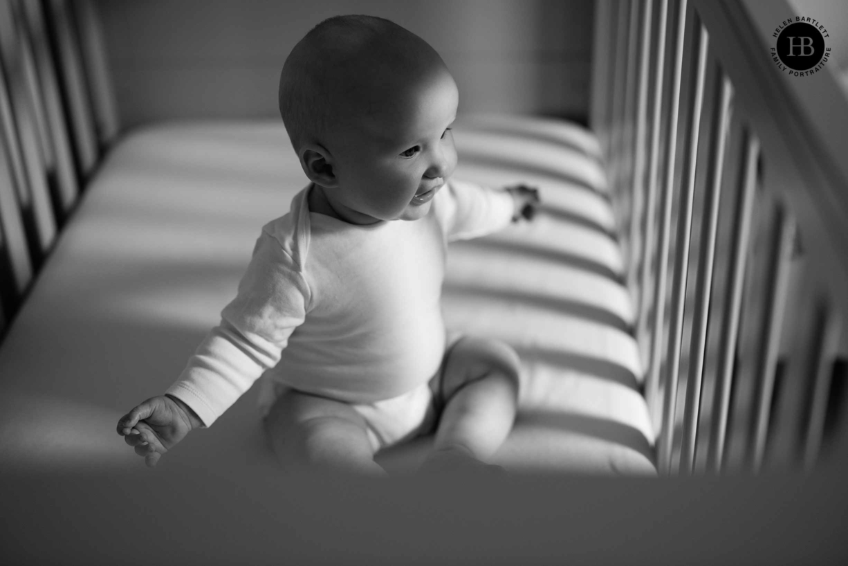baby-sits-cot-beautiful-shadows-and-light-during-in-home-baby-photo-shoot-islington