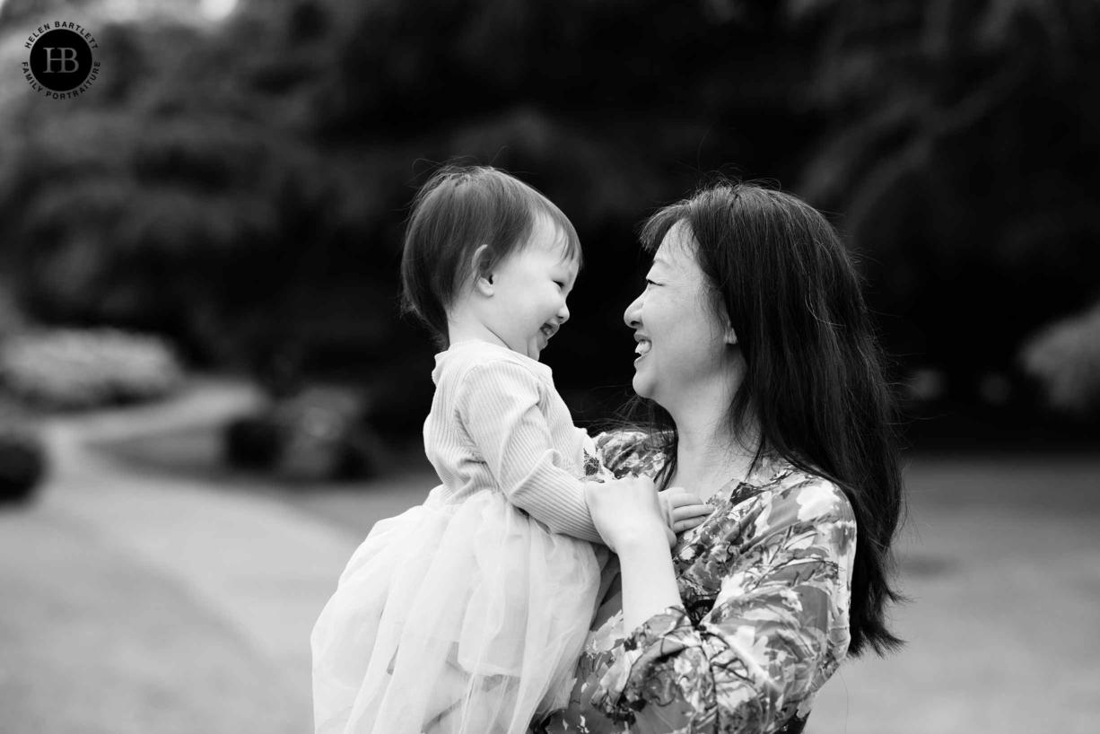 mum hugs daughter in flower garden in greenwich park on family photo shoot