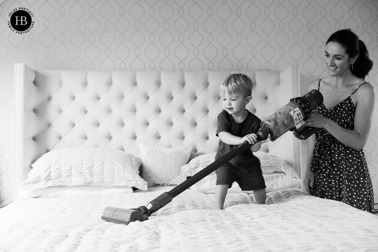 child plays with toy dyson hoover during family photo shoot in clapham