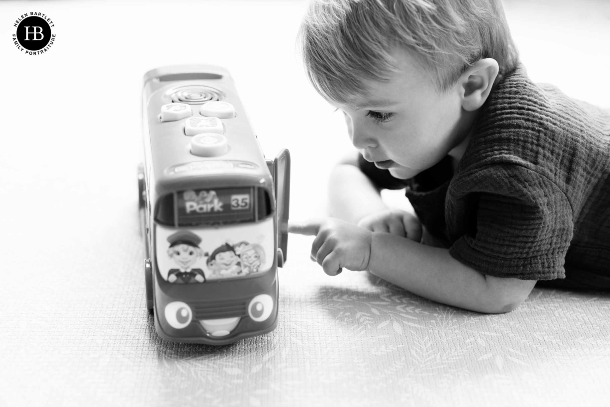 black and white professional photo of little boy playing with toy bus