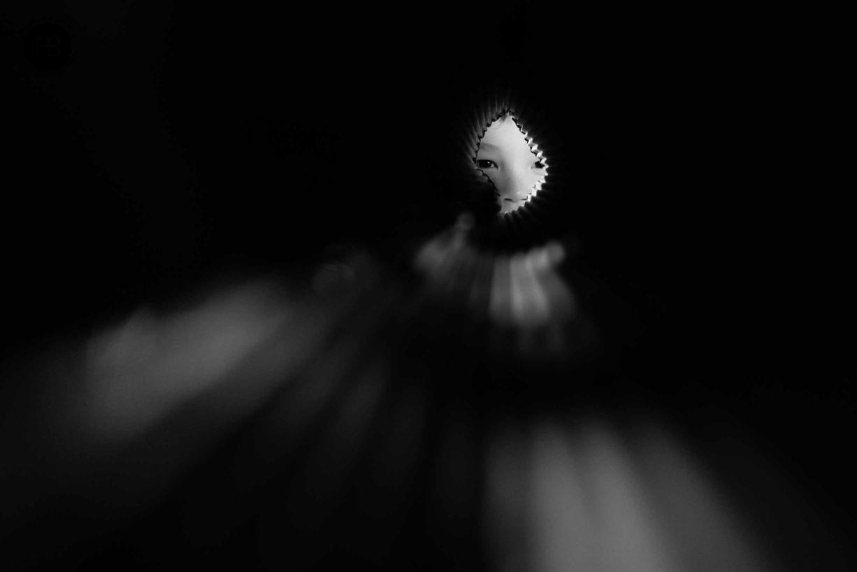 boy looks through cardboard tube shot in monochrome