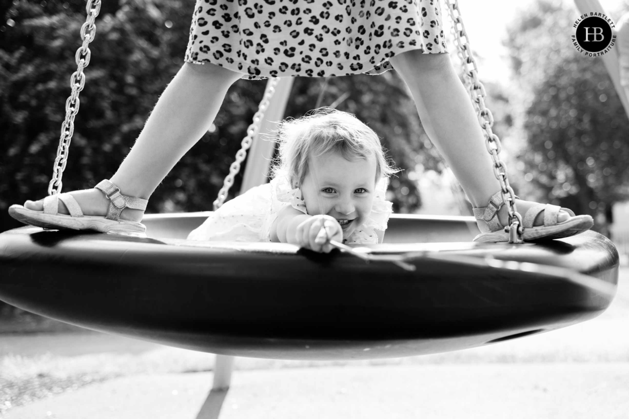 two girls play on the swings during a photo shoot of family photography in east London