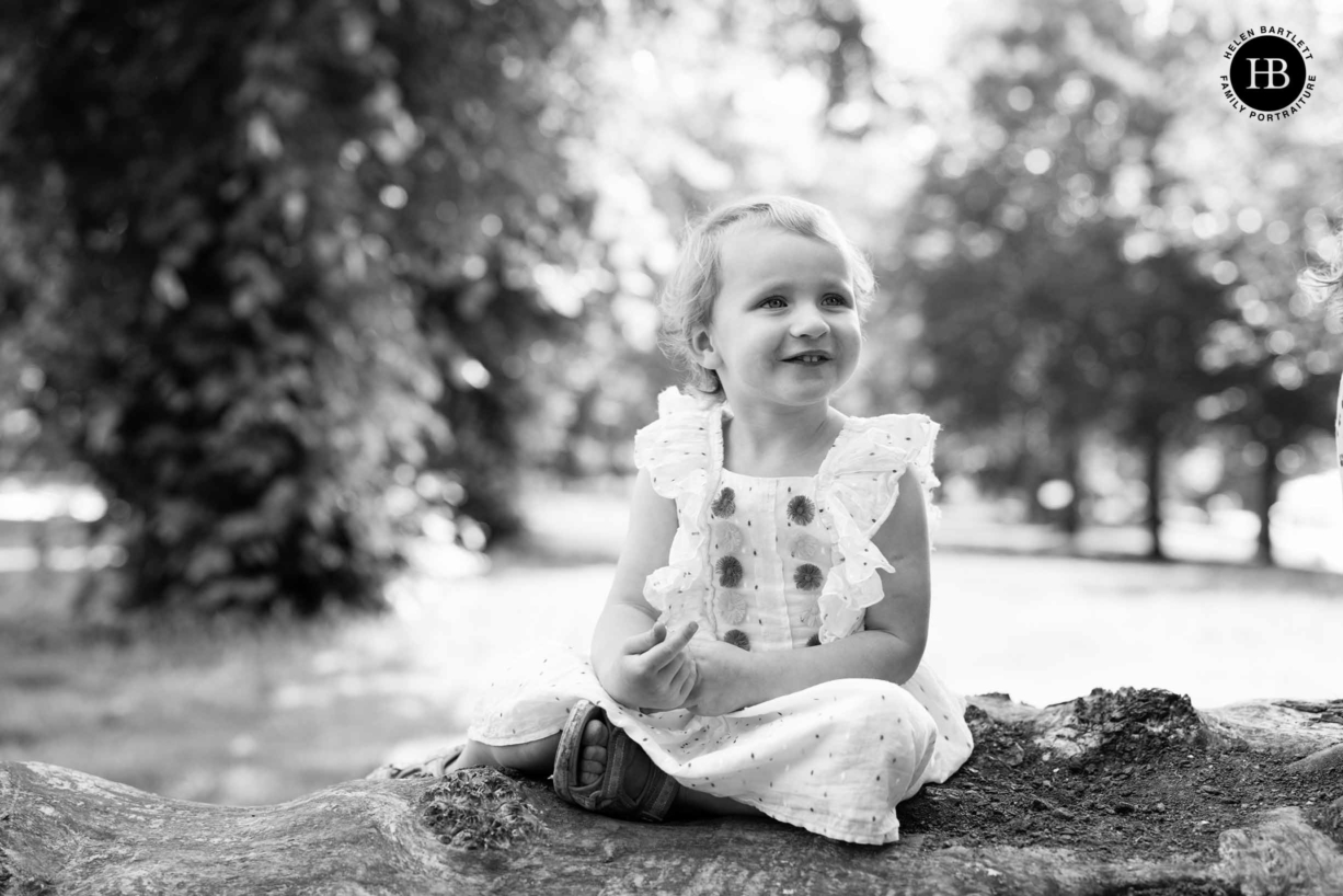 little girl sits on a fallen tree in Victoria park during an east London family photography session