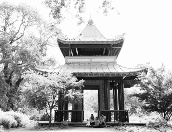 family sit by Chinese pavilion in Victoria Park on East London family photography session
