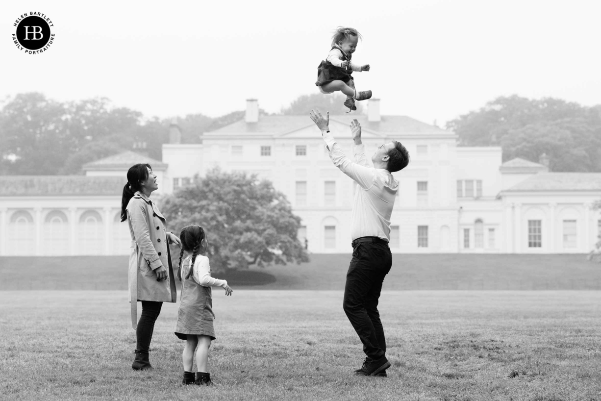 family pictures in front of Kenwood House on Hampstead Heath. Dad throws baby in the air while mum and older daughter look on.