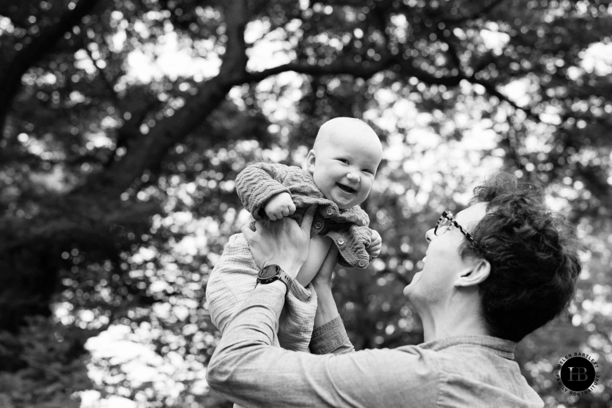 dad holds baby in the air and they both laugh in beautiful black and white family photo