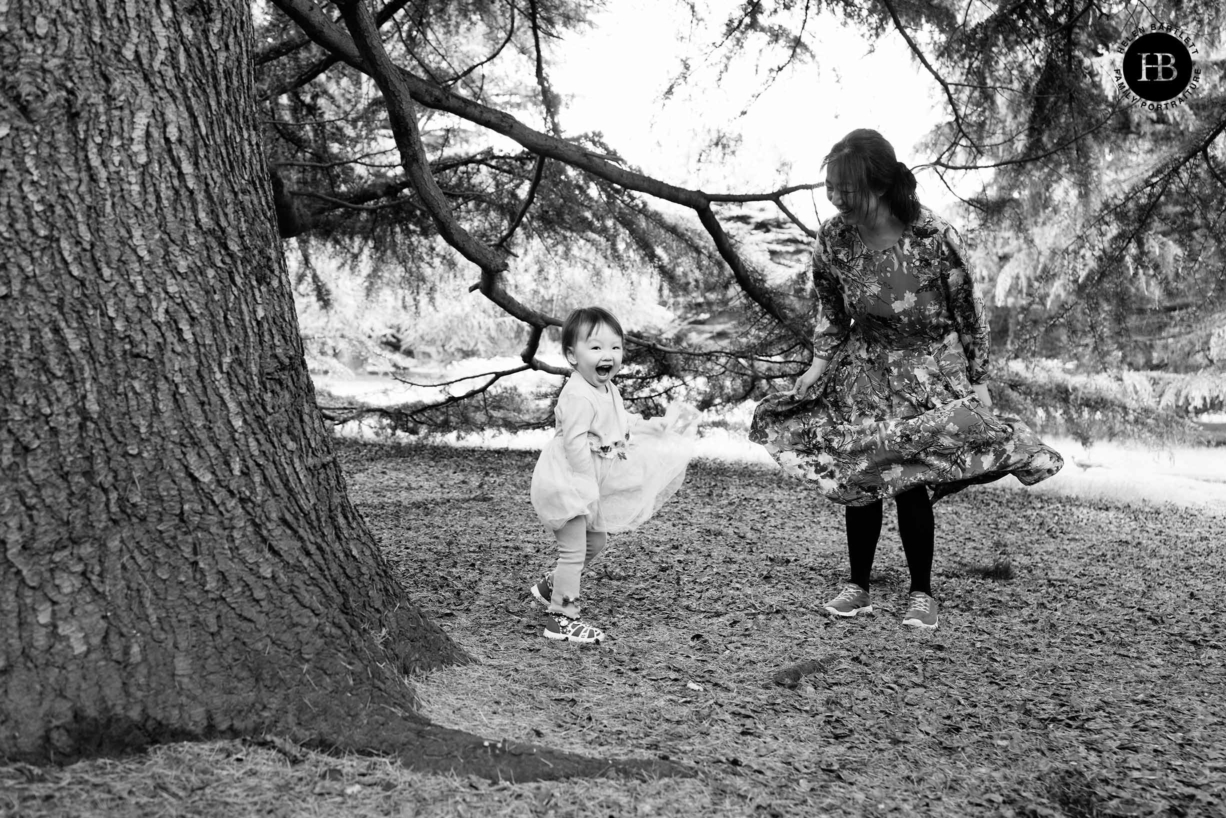 little girl and mum dance and swish skirts during greenwich park family photography
