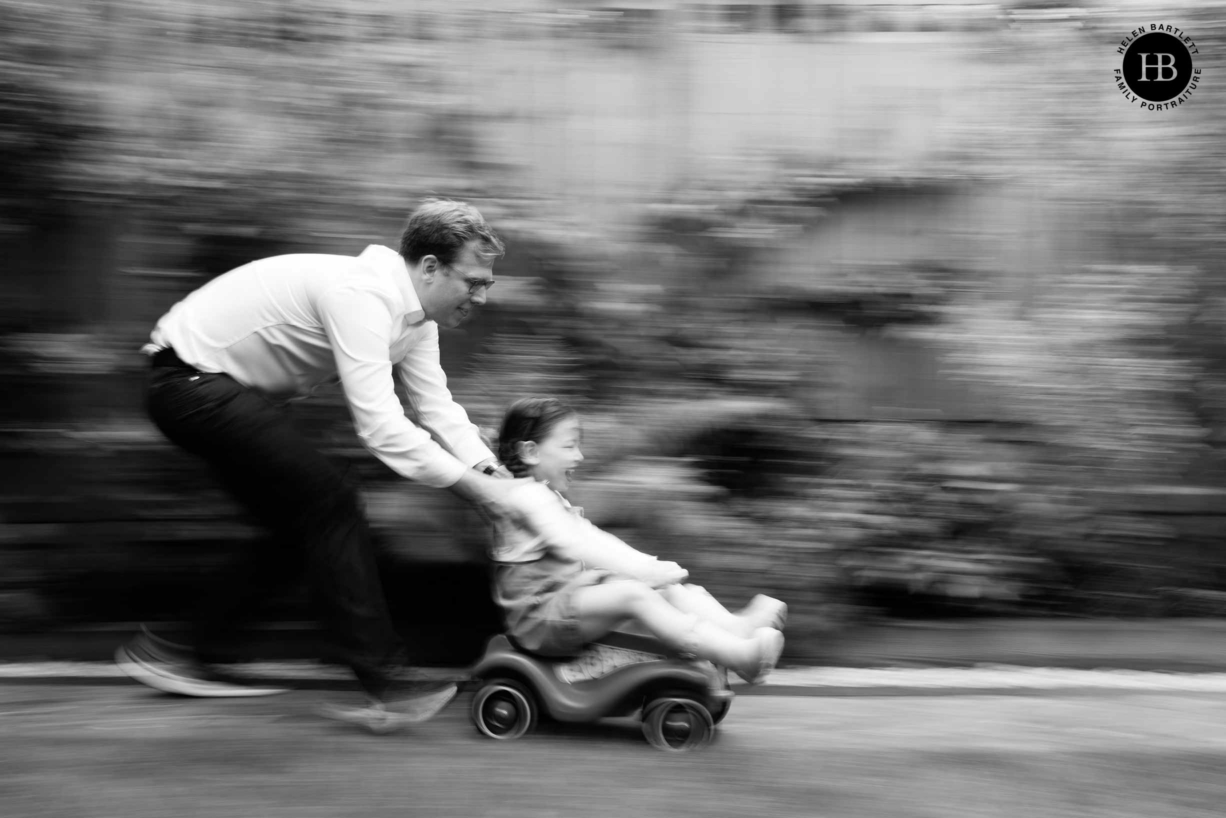 Dad pushes daughter on toy car in Hampstead Garden. Panning technique used to show speed in the photograph.