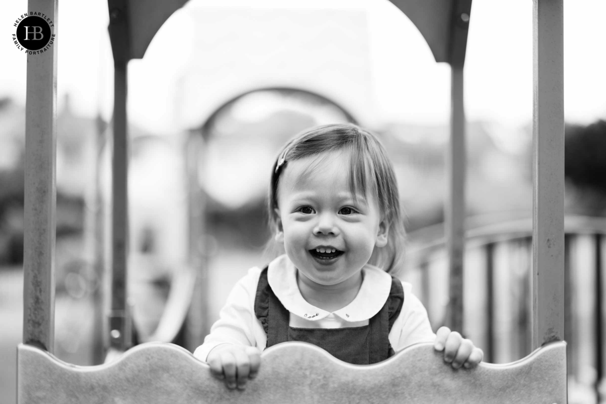 Portrait of two year old girl laughing while playing on the climbing frame
