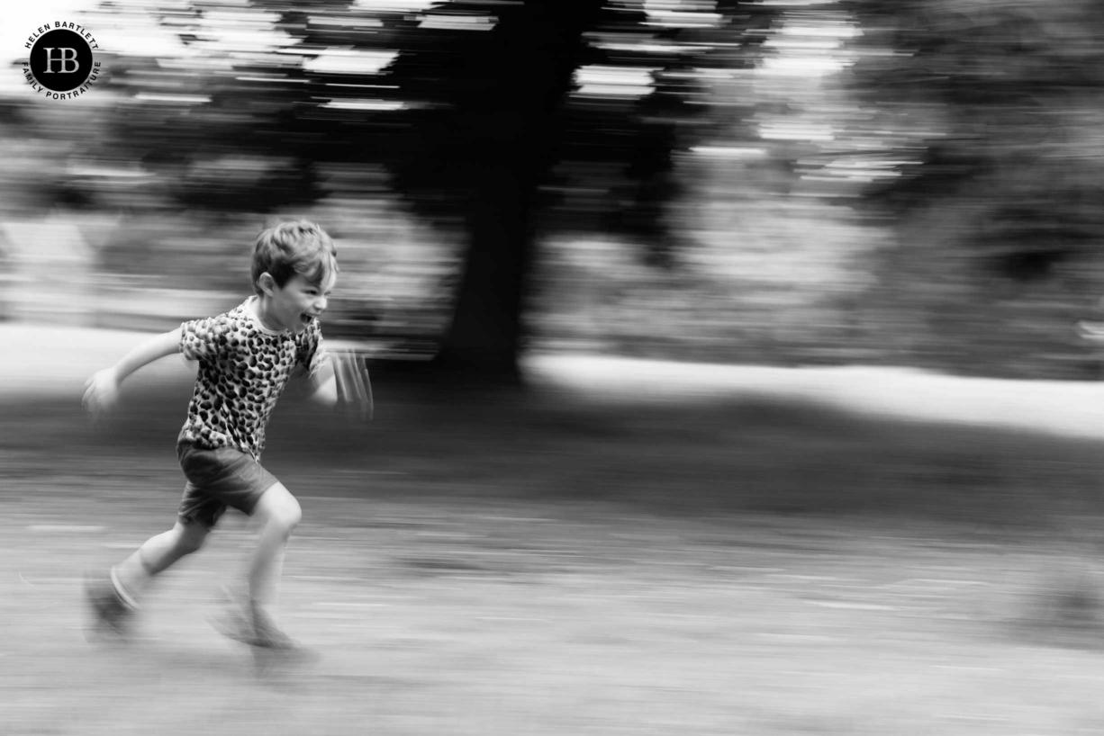 Little boy runs through greenwich park, professional photo using panning technique to show movement