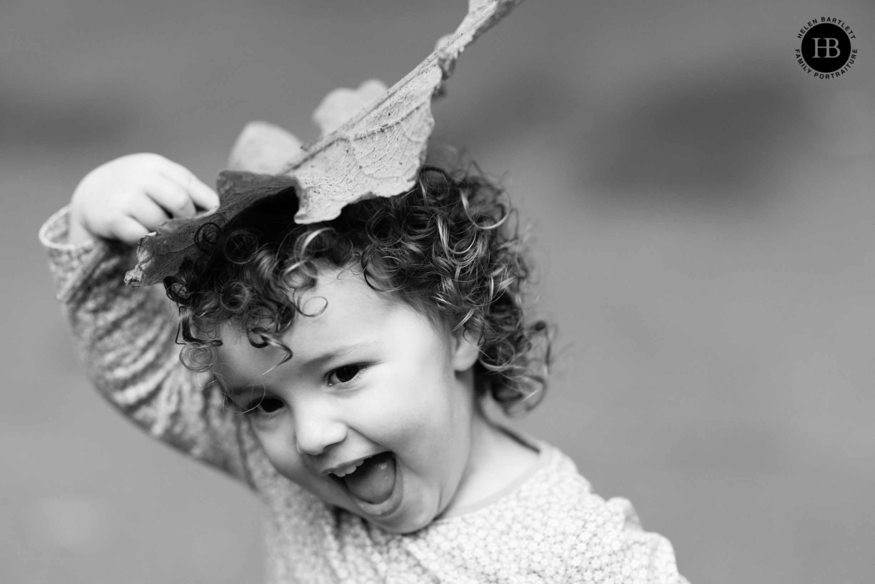 little girl laughs as she uses a leaf for a hat during a family photo shoot in Greenwich Park