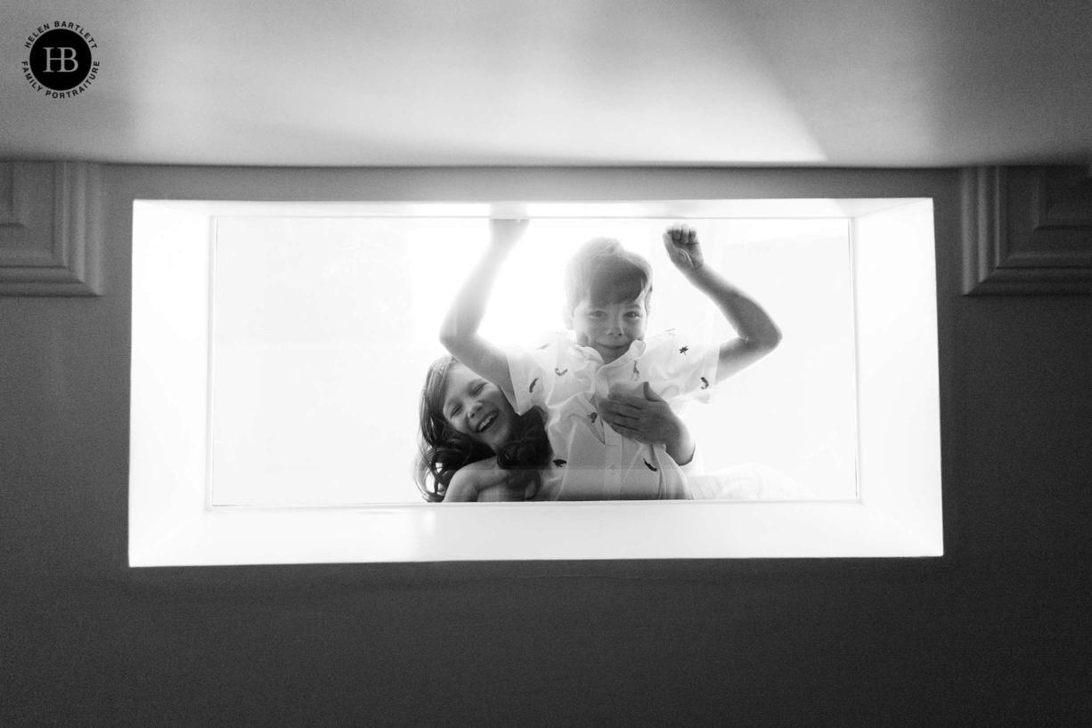 children look down through skylight into basement room