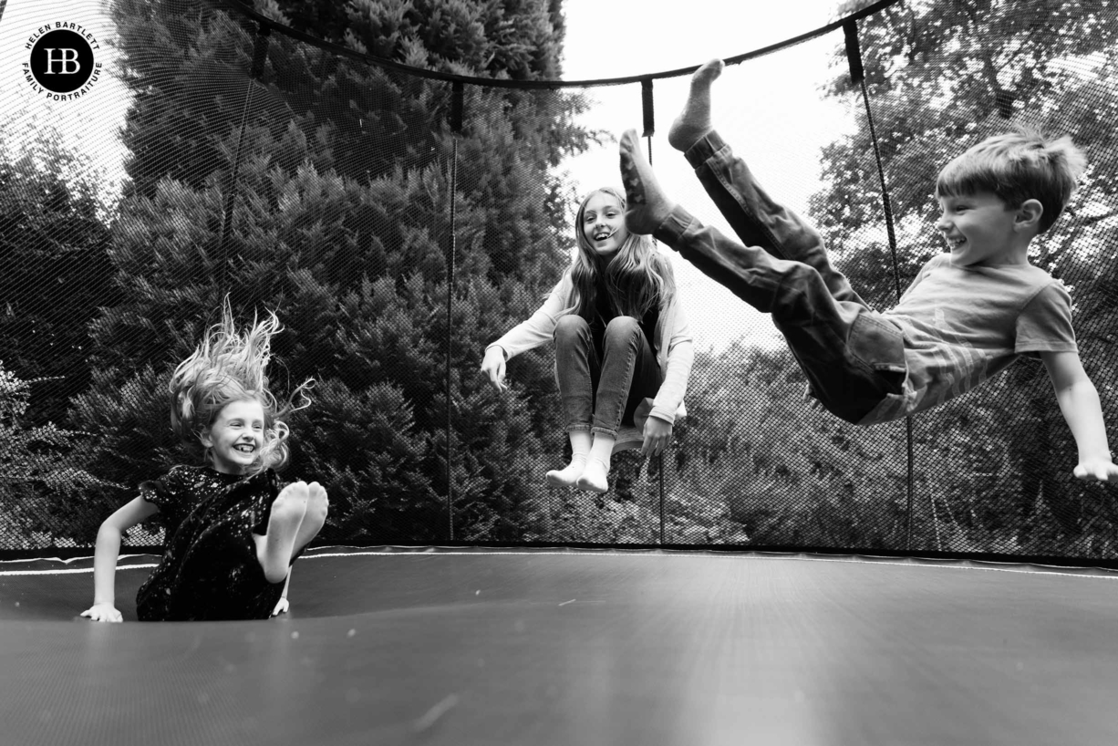 children jump on trampoline during family photo shoot in beaconsfield