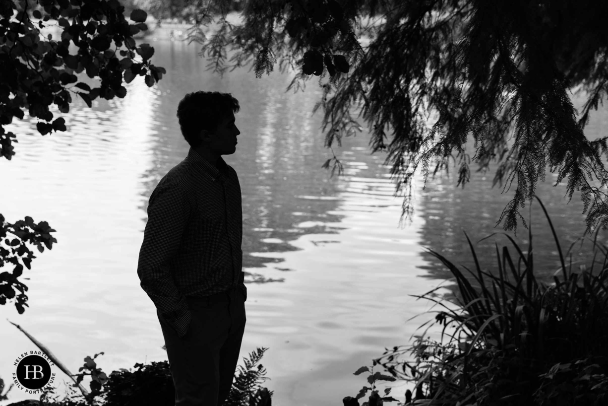 silhouette of teenage boy by the lake at kew