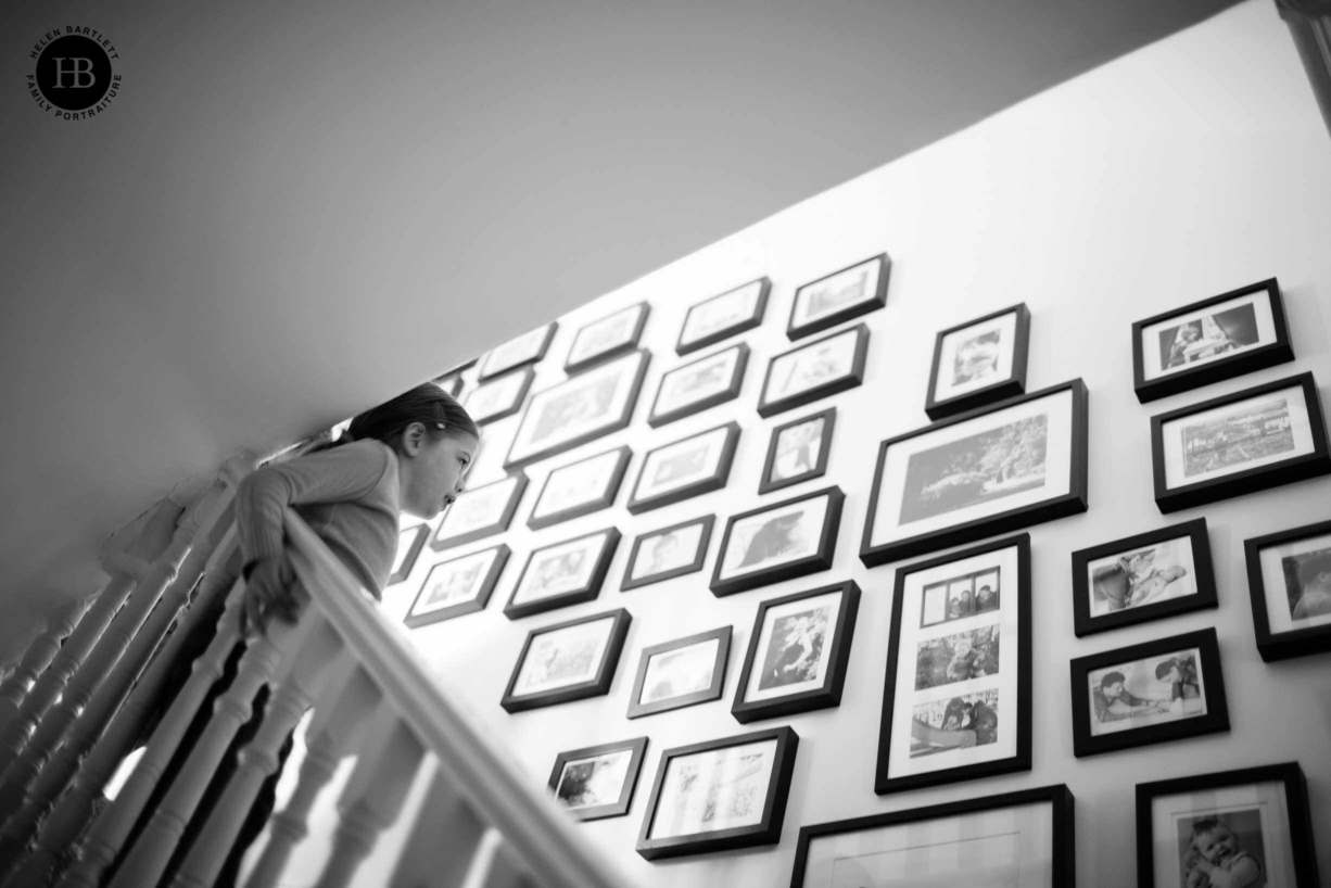 little girl looks at wall display of framed family photos