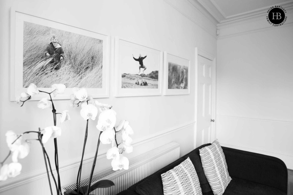 three framed family photos displayed on the living room wall